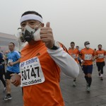 Participants wearing masks during a hazy day at the Beijing International Marathon in front of Tiananmen Square, in Beijing